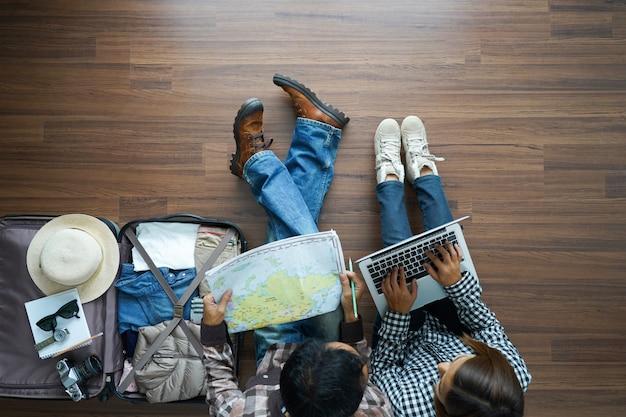 Visão aérea do casal jovem do viajante planejamento com trabalhando no laptop
