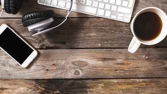 Visão aérea do celular; fone de ouvido e teclado com xícara de café