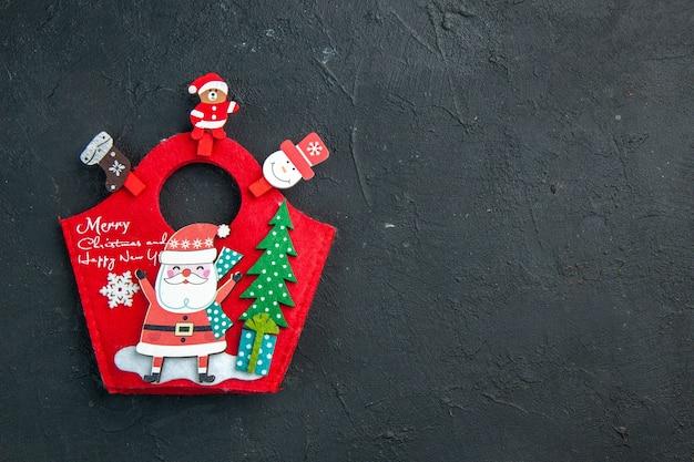 Visão aérea do clima de natal com acessórios de decoração e caixa de presente de ano novo na superfície escura