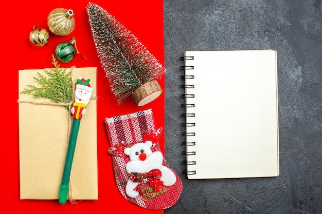Visão aérea do clima de natal com meia de presente de acessórios de decoração de árvore de natal ao lado do caderno em fundo vermelho e preto