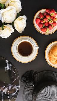 Visão aérea do copo de chá com morangos e pão