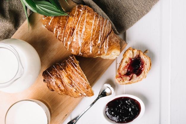 Visão aérea do croissant com geléia de frutas e leite na mesa branca