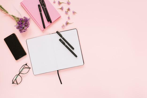 Visão aérea do diário; canetas; óculos; celular e óculos no fundo rosa