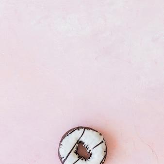 Visão aérea do donut de chocolate branco sobre fundo rosa