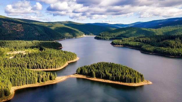Visão aérea do drone da natureza na romênia. colinas com floresta exuberante, vale com lago