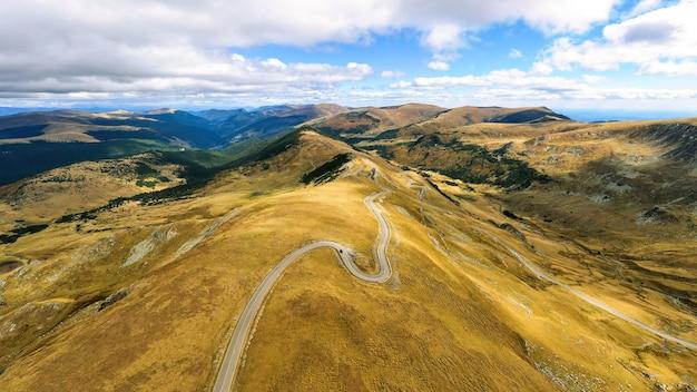 Visão aérea do drone da natureza na romênia. montanhas dos cárpatos, vegetação esparsa, estrada com carro