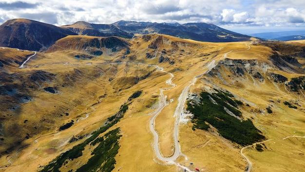Visão aérea do drone da natureza na romênia. montanhas dos cárpatos, vegetação esparsa, estrada