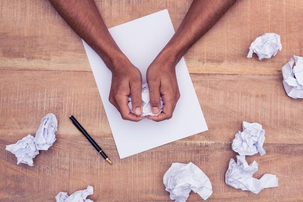 Visão aérea do empresário fazendo bolas de papel na mesa no escritório