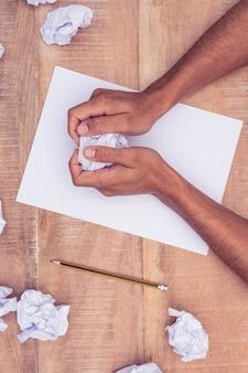 Visão aérea do empresário pelo bloco de notas fazendo bolas de papel na mesa no escritório
