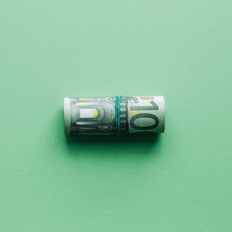 Visão aérea do enrolado nota de cem euros na superfície verde