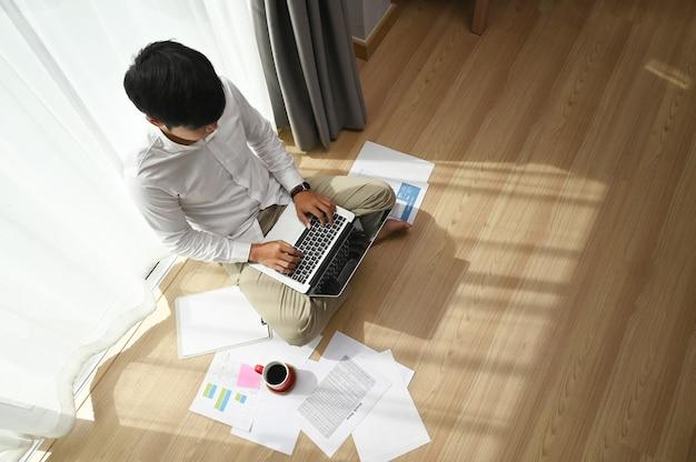 Visão aérea do freelancer jovem usando laptop enquanto está sentado ao lado da janela em casa.