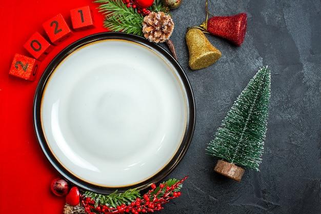 Visão aérea do fundo de ano novo com acessórios de decoração de prato de jantar ramos de abeto e números em um guardanapo vermelho ao lado da árvore de natal em uma mesa preta