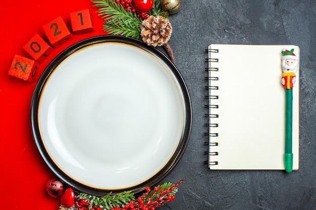 Visão aérea do fundo de ano novo com acessórios de decoração de prato de jantar ramos de abeto e números em um guardanapo vermelho ao lado do caderno com caneta em uma mesa preta