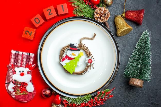 Visão aérea do fundo de ano novo com fita vermelha na placa de jantar decoração acessórios ramos de abeto e números meia de natal em um guardanapo vermelho ao lado da árvore de natal em uma mesa preta