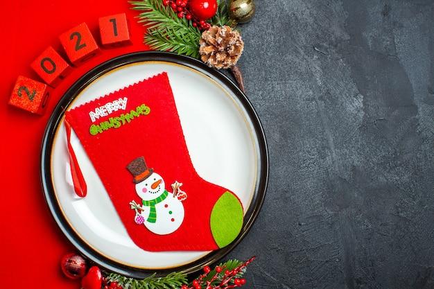 Visão aérea do fundo do ano novo com a meia de natal no prato de jantar acessórios de decoração ramos de abeto e números em um guardanapo vermelho sobre uma mesa preta