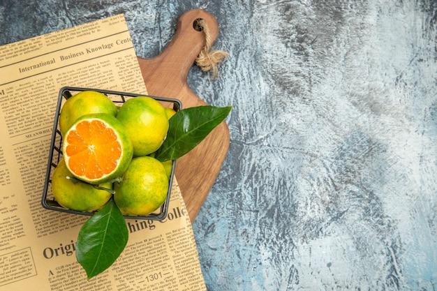 Visão aérea do jornal de frutas cítricas frescas na tábua de madeira em fundo cinza