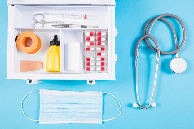Visão aérea do kit de primeiros socorros médicos e equipamentos médicos em fundo azul