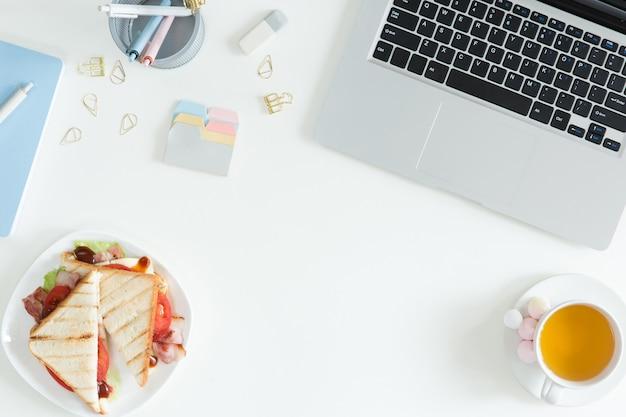 Visão aérea do laptop, sanduíche fresco, xícara de chá verde e telefone móvel na mesa branca do desktop. negócios de mulher e conceito de café da manhã, vista superior e plana leigos
