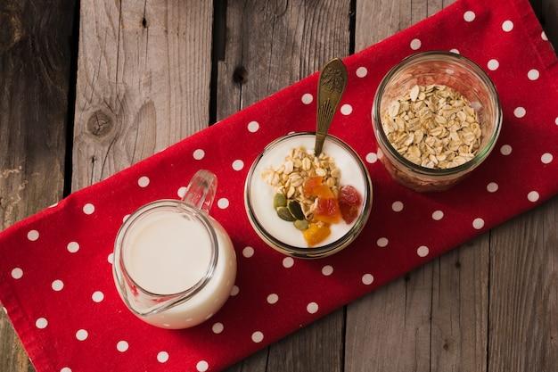 Visão aérea do leite, iogurte e aveia seca no pote de vidro no guardanapo vermelho sobre a mesa de madeira