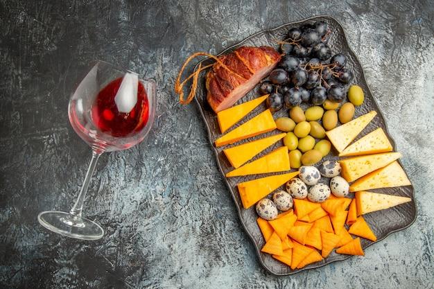 Visão aérea do melhor lanche saboroso em uma bandeja marrom e uma taça de vinho caída no fundo de gelo