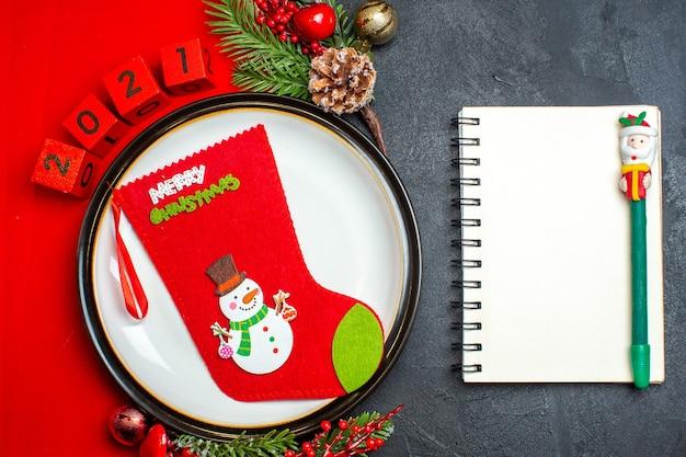 Visão aérea do plano de fundo de ano novo com meia de natal no prato de jantar acessórios de decoração ramos de abeto e números em um guardanapo vermelho ao lado do caderno com caneta em uma mesa preta