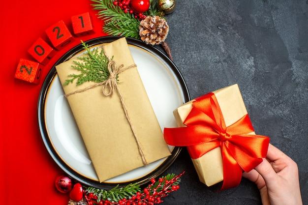 Visão aérea do plano de fundo do ano novo com o presente no prato de jantar acessórios de decoração ramos de abeto e números em um guardanapo vermelho sobre uma mesa preta