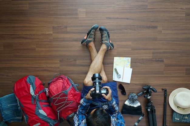 Visão aérea do plano de homem viajante e planejamento de mochila