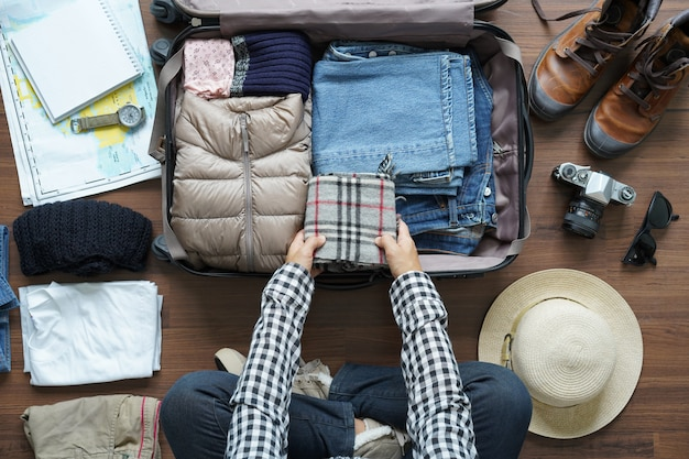 Visão aérea do plano de mulher viajante e planejamento de mochila