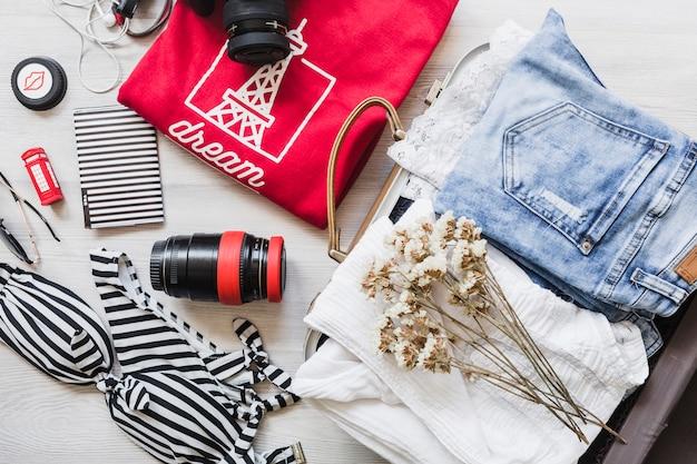 Visão aérea do saco de viagem com roupas femininas e flores
