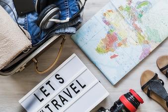 Visão aérea do saco de viagem, mapa, câmera e par de calçado na mesa de madeira