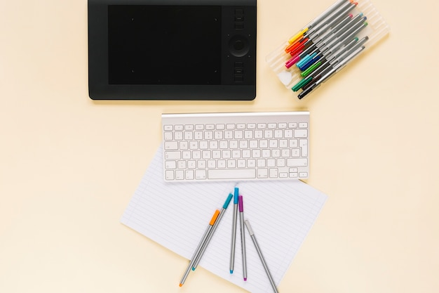 Visão aérea do tablet digital gráfico com teclado e canetas de feltro no caderno sobre o fundo bege