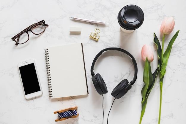 Visão aérea do telefone celular; óculos; caderno; papelaria; fone de ouvido e tulipas cor de rosa no pano de fundo de mármore