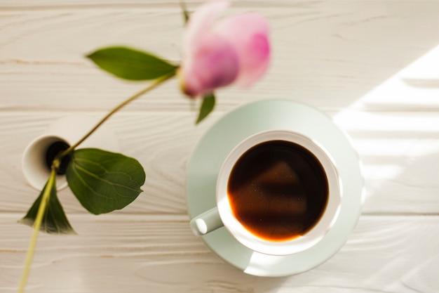 Visão aérea do vaso de flor e café preto na mesa de madeira branca
