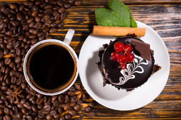 Visão aérea dos grãos de café ao lado da caneca branca e sobremesa decorada com chocolate e frutas vermelhas em uma mesa de madeira