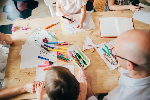 Visão aérea família desenho interior com lápis de cor