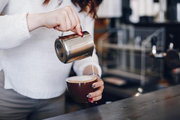 Visão aérea feminino barista derramando espuma de leite em cappuchino no café