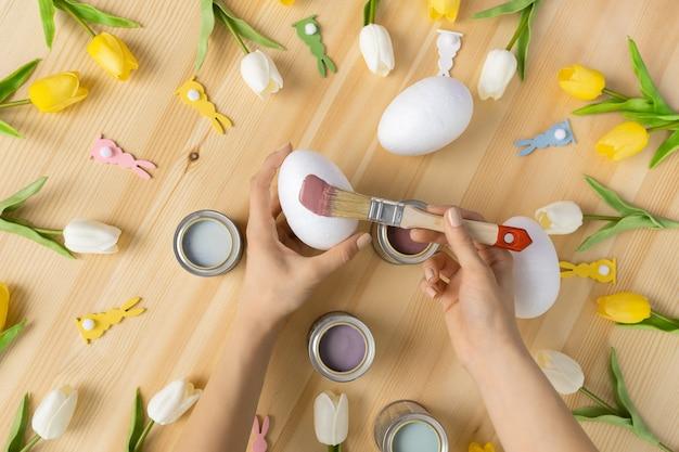 Visão aérea na mão da menina pintando ovos de páscoa na mesa de madeira conceito de escova de cor de fundo de cor tradicional
