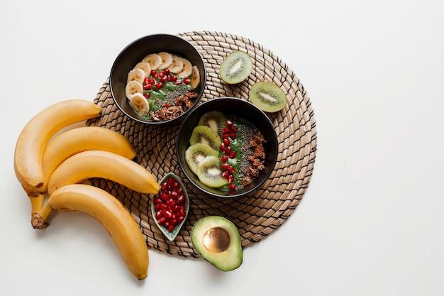 Visão aérea no prato da tigela de suco verde coberto com abacate e espinafre, sementes de romã e granola.