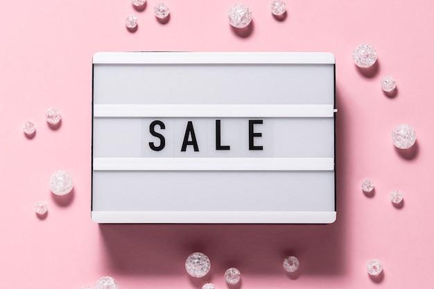 Visão aérea plana leiga criativa do texto de venda na mesa de luz e decorações brilhantes sobre fundo rosa. venda festiva e conceito de promoção. sexta-feira preta