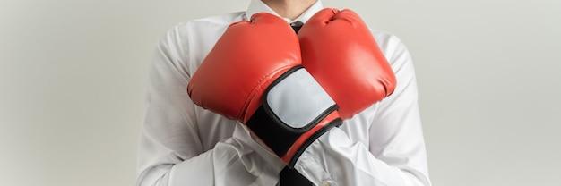 Visão ampla frontal do empresário usando luvas de boxe vermelhas com os braços cruzados sobre o peito.