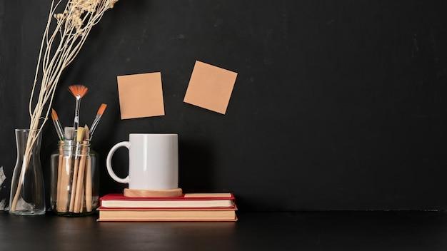 Visão aproximada da área de trabalho com livros, pincéis e uma xícara de café