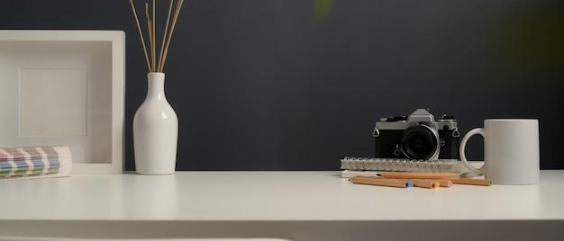 Visão aproximada da mesa de trabalho com artigos de papelaria, câmera, suprimentos, simulação de quadro e decoração no escritório doméstico