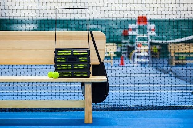 Visão aproximada da quadra de tênis através da rede, bolas e raquete