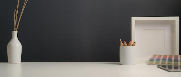 Visão aproximada do espaço de trabalho com artigos de papelaria, amostra de cor, simulação de quadro, vaso de planta e espaço de cópia na mesa branca