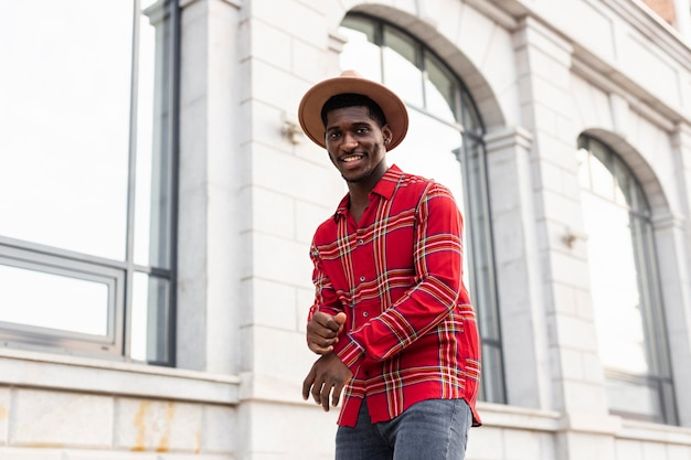 Visão baixa de um homem de camisa vermelha ao lado de um prédio