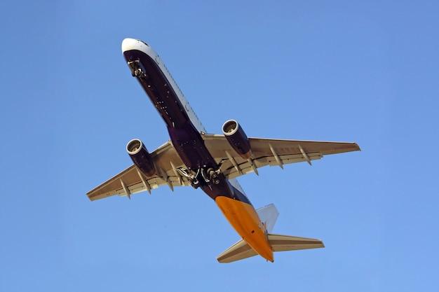 Visão completa abaixo de um avião comercial em voo.