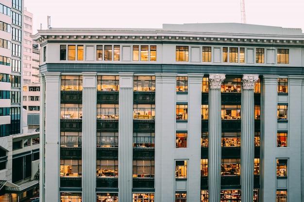 Visão completa de um moderno edifício branco com colunas e gravuras nelas com janelas e luzes