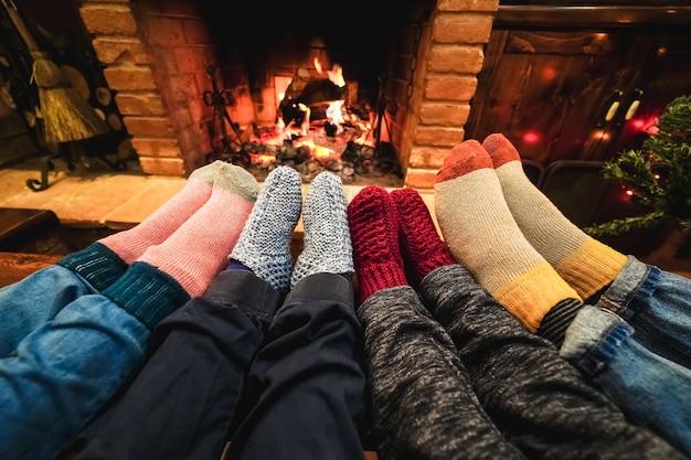 Visão das pernas de uma família feliz usando meias quentes em frente à lareira aconchegante - foco nas meias esquerdas
