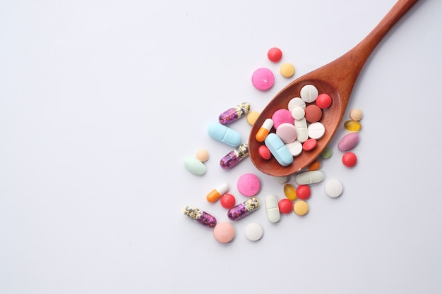 Visão de alto ângulo de comprimidos e cápsulas em colher em fundo branco