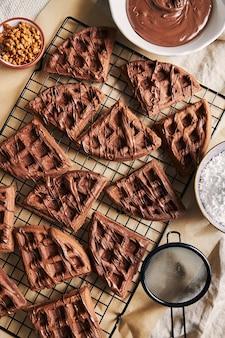 Visão de alto ângulo de deliciosos waffles de chocolate em uma rede na mesa perto dos ingredientes